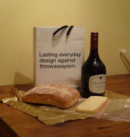 "Wine, cheese and bread with a box saying ""Lasting everyday design against throwawayism"""